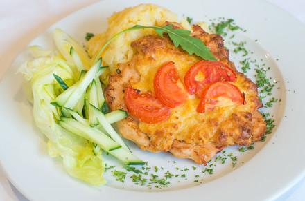 Kuřecí steak se sýrovou krustou a rajčaty podávaný s jemnou bramborovou kaší a domácí tatarkou.