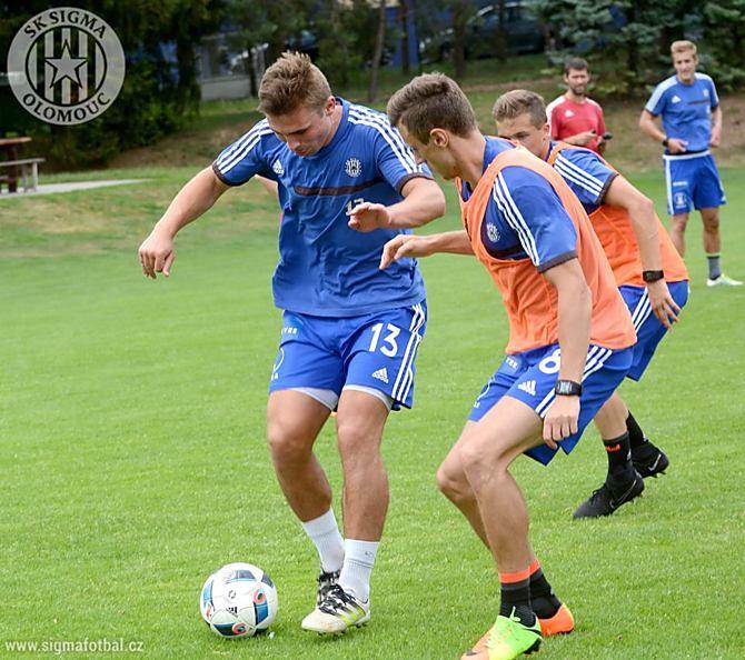 Zdeněk Linhart si na tréninku ve Slatinicích snaží pokrýt míč před Šimonem Faltou.
