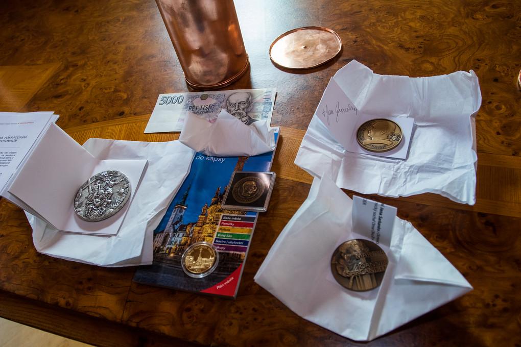 Z roku 2018 bude na nálezce v budoucnosti čekat celá řada předmětů: třeba pamětní medaile, vydané při příležitosti zápisu Sloupu Nejsvětější Trojice do seznamu UNESCO, unikátní medaile, vydaná při příležitosti svěcení Jana Sarkandra během návštěvy papeže Jana Pavla II. či mince, připomínající výročí intronizace arcibiskupa Jana Graubnera. V tubusu jsou také současné propagační materiály města a pětitisícová bankovka.